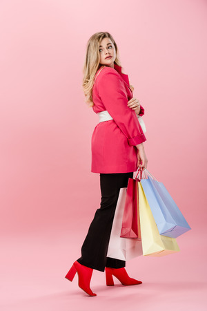 side view of stylish young oversize woman holding paper bags and looking away on pink