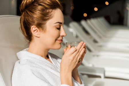 side view of happy young woman holding cup of herbal drink while resting on sunbed in spa