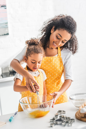 african american mother and daughter whisking eggs for dough together in kitchen