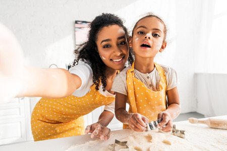camera point of view of smiling african american mother and daughter in aprons preparing cookies in kitchen