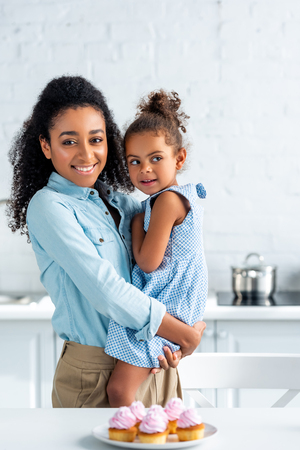 happy african american mother hugging daughter in kitchen, cupcakes on table