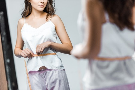 cropped view of woman measuring her waistline and looking at mirror Stock Photo - 111911599