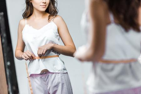 Vista recortada de la mujer midiendo su cintura y mirando en el espejo