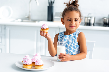 adorable african american child holding cupcake and glass of milk in kitchen