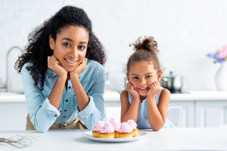 cheerful african american mother and daughter resting chins on hands and looking at camera, cupcakes on table in kitchen