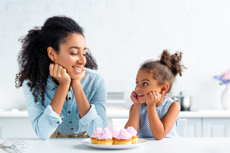 cheerful african american mother and daughter resting chins on hands and looking at each other, cupcakes on table in kitchen Stock Photo