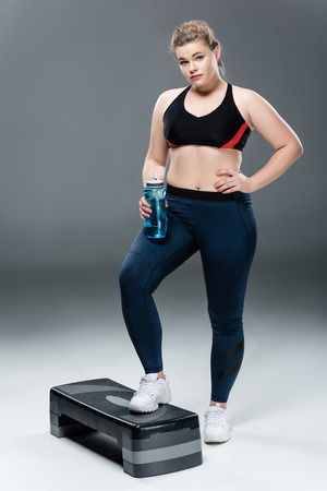 young overweight woman in sportswear holding bottle of water and standing on step platform on grey