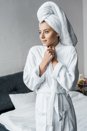 attractive dreamy girl in white bathrobe standing in bedroom