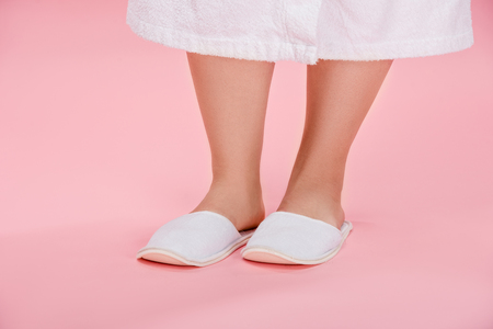cropped shot of young overweight woman in white slippers and bathrobe standing on pink Reklamní fotografie