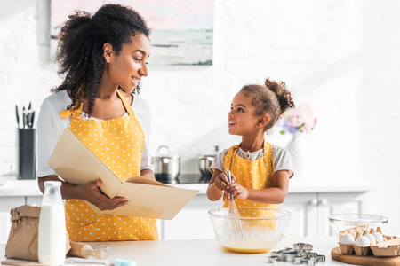 african american mother holding cookbook and daughter preparing dough in kitchen, looking at each other