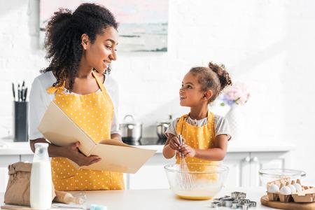Madre afroamericana sosteniendo libro de cocina e hija preparando masa en la cocina, mirarse Foto de archivo
