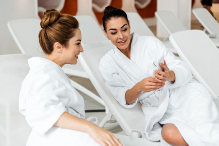 Happy young women looking at smartphone while lying together on sunbeds in spa