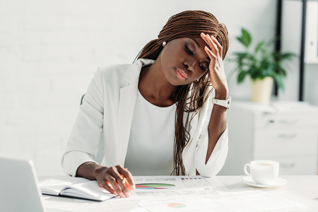 Tired African american adult businesswoman sitting at desk and working on project in office