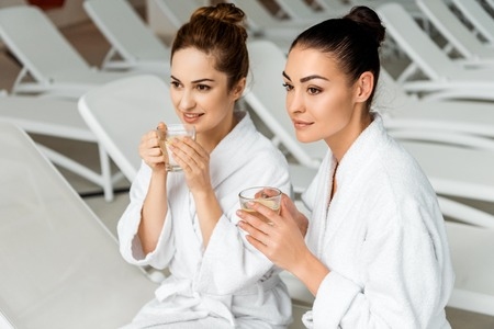 Beautiful young women in bathrobes holding cups with herbal tea in spa
