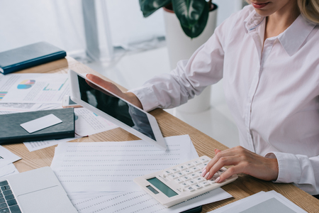 Partial view of businesswoman with tablet making calculations at workplace with papers