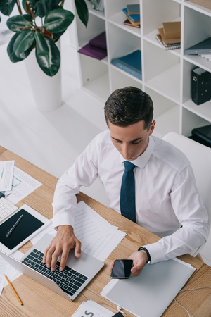 High angle view of businessman using smartphone and laptop at workplace with documents in office
