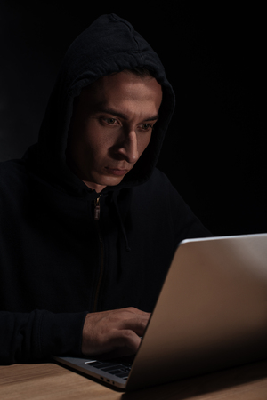 Hacker in black hoodie using laptop, cuber security concept