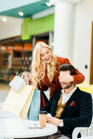 Excited fashionable girl with shopping bags closing eyes and making surprise for boyfriend