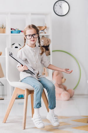 Little child in eyeglasses with clipboard sitting on chair and looking at camera Stock fotó