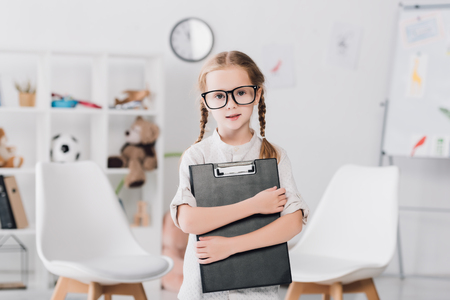 Little child in eyeglasses holding clipboard and looking at camera Stock fotó