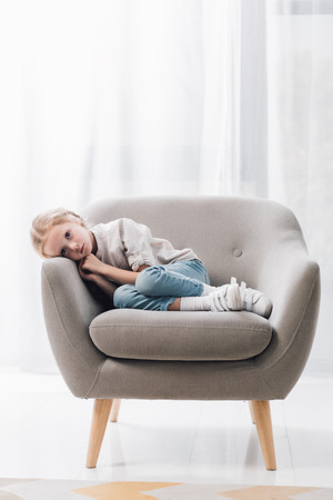 Depressed little child lying in armchair alone Stock fotó