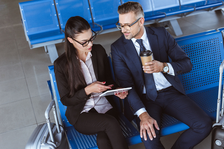 Adult businessman drinking coffee while businesswoman using digital tablet at departure lounge in airport Imagens
