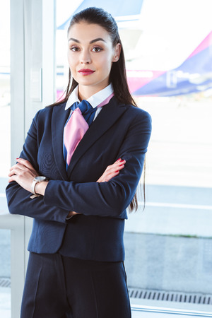 Adult female airport worker standing with arms crossed near window