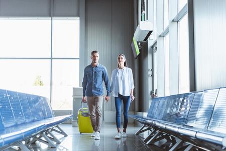 Romantisches Paar, das Händchen hält und mit gelbem Gepäck im Flughafen spazieren geht?