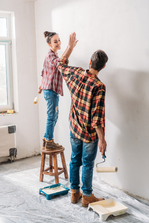 High angle view of young couple giving high five while painting wall in new apartment