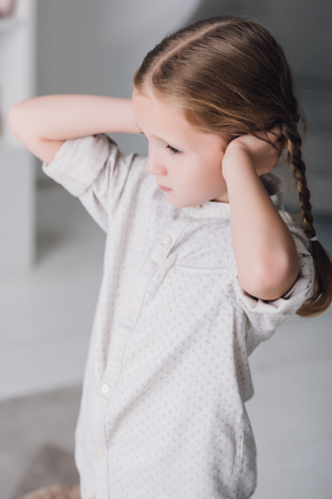 Depressed little child covering ears with hands