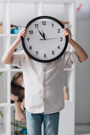 Little child covering face with big clock Фото со стока - 112347281