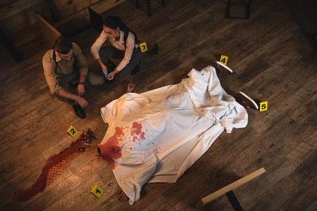 Female and male detectives investigating dead body covered with white sheet at crime scene Banque d'images