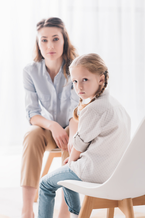 Adult psychologist and depressed little child looking at camera in office