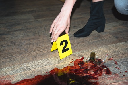 Cropped view of hand touching evidence mark at bloody crime scene