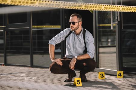 Thoughtful male detective sitting at crime scene 版權商用圖片