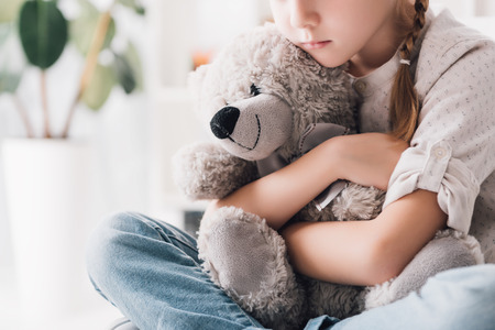 Cropped shot of depressed little child embracing her teddy bear Stockfoto