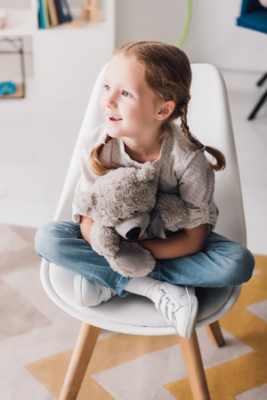 Happy little child sitting on chair and embracing her teddy bear