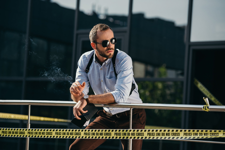 Male detective in sunglasses smoking and looking  to the side leaning on the fence
