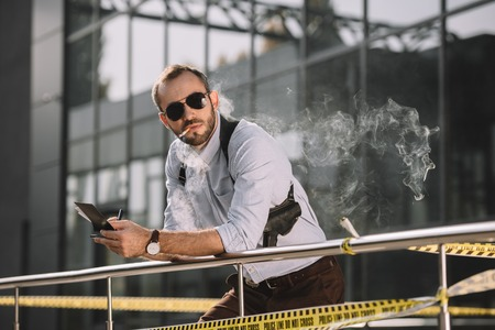 Male detective smoking and making notes leaning on the fence