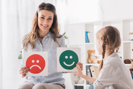 Smiling psychologist showing happy and sad emotion faces cards to child