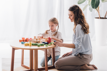 Side view of happy mother playing blocks with adorable little child