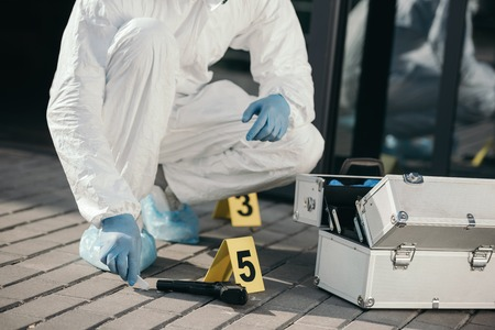 Cropped view of male criminologist in protective suit and latex gloves sitting near evidence gun 版權商用圖片