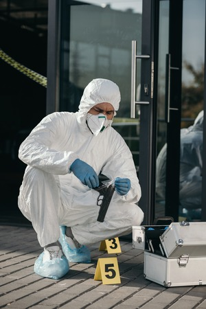 Male criminologist in protective suit and latex gloves sitting with evidence gun in arms