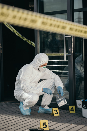 Male criminologist in protective suit and latex gloves packing evidence with tweezers at crime scene