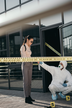 Female detective taking from criminologist new key evidence