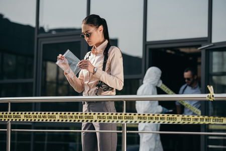 Female detective standing and looking at evidence in package