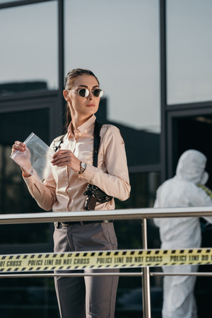 Female detective with evidence package in hands Stock Photo - 112347494