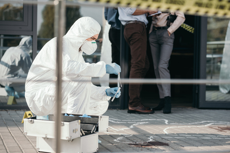 Male criminologist in protective suit and latex gloves collecting evidence at crime scene 版權商用圖片