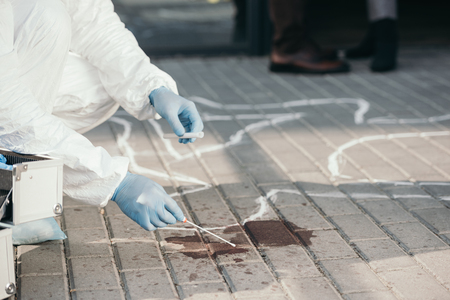 Male criminologist in protective suit and latex gloves collecting blood sample at crime scene
