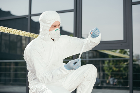 Male criminologist in protective suit and latex gloves looking at evidence at crime scene